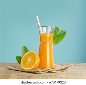 Glass of fresh orange juice with group of orange on wooden box on blue sky background with copy space
