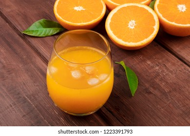 A glass of fresh orange juice with orange halves and leaves on a dark rustic wooden background with a place for text