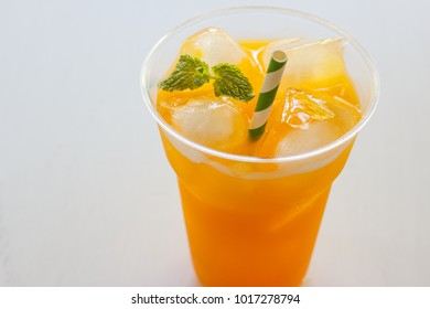 Glass of fresh orange juice on white table.