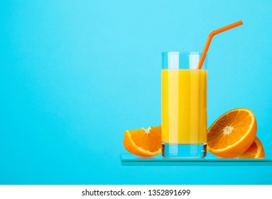 Glass of fresh orange juice on a blue background. Copy space.