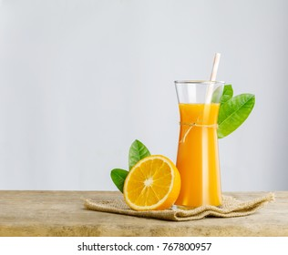 Glass of fresh orange juice with orange on wooden table isolate on white background with copy space