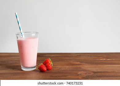 Glass of fresh protein shake on table against white background