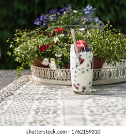 Glass with fresh raspberries, blueberries and yogurt stands on a table with a romantic old tablecloth. Shot in the garden.