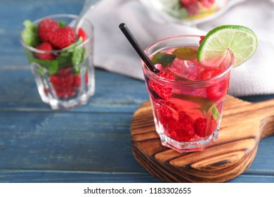 Glass of fresh raspberry mojito on wooden table