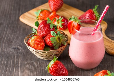 Glass of fresh strawberry milkshake, smoothie and fresh strawberries on pink, white and wooden background. Healthy food and drink concept.