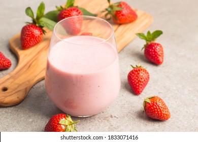 Verre de milkshake aux fraises fraîches, smoothie et fraises fraîches sur fond rose, blanc et bois. Concept de nourriture et de boisson saine.