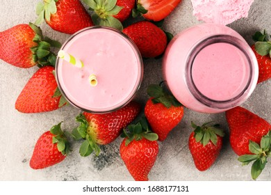 Glass of fresh strawberry shake, smoothie or milkshake and fresh strawberries on table. Healthy food and drink concept with juicy fruits