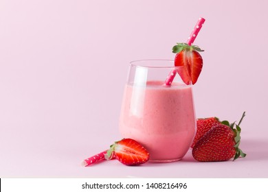 A glass of fresh strawberry smoothie on a wooden background. Summer drink shake, milkshake, juice and refreshment organic concept.