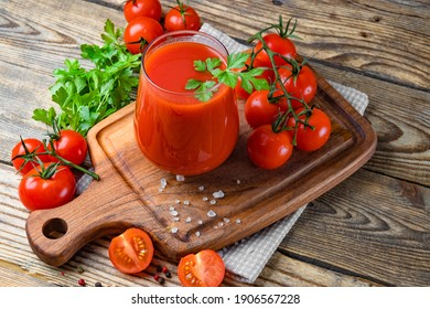 Glass of fresh tomato juice and tomatoes on the wooden background