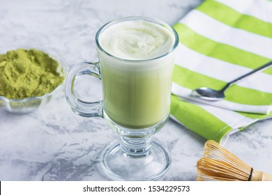A glass of freshly made green tea latte. Unusual recipe with matcha tea and soy milk. A healthy veggie drink.