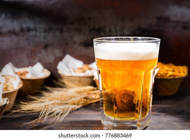 Glass with freshly poured beer near plates with pistachios, small pretzels and peanuts on dark wooden desk. Food and beverages concept