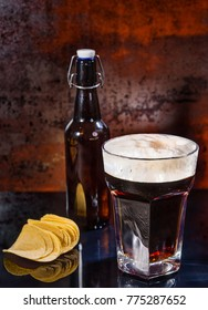 Glass with freshly poured dark beer, beer bottle near scattered chips on a black mirror surface. Food and beverages concept