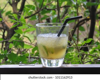 "A glass of freshly prepared rum-based cocktail ""Ti Punch"" (Petit Punch) with a black straw in a garden setting in Mauritius Island"