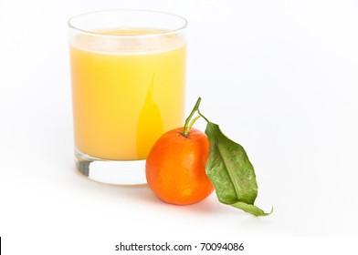 Glass of freshly squeezed orange juice and a single orange fruit with a leaf on isolating background