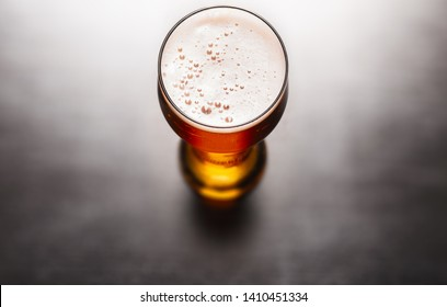 Glass of frothy fresh beer on table