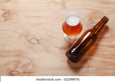 Glass full of amber beer and a beer bottle on a textured wooden surface