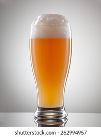 Glass full of beer and foam on a gray background