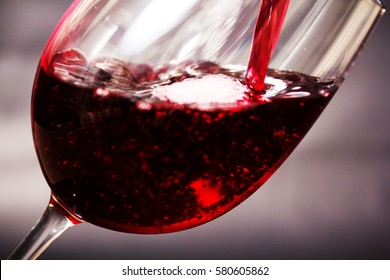 Glass of full bodied red wine being poured from bottle