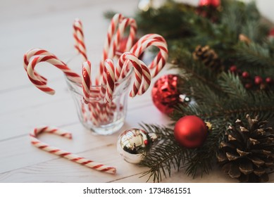Glass full of candy canes on white table with Christmas decorations..