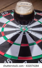 Glass full of dark ale standing on a darts game target