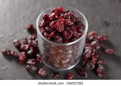 Glass full of dried cranberries on a black slate plate, selective focus