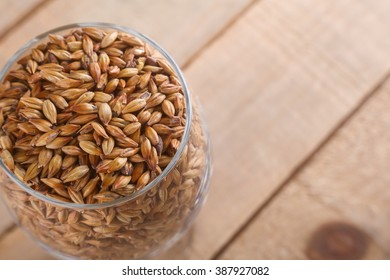 Glass full of malted barley over a wooden background