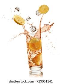 glass full of orange drink with orange slices and ice cubes falling and splashing, on white background