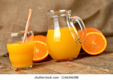 Glass full of orange juice, carafe with fresh juice, straw and fresh oranges in the background on wooden table