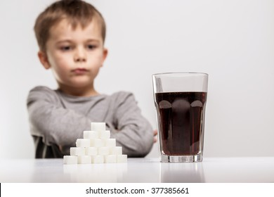 Glass full of soft drink, next to it is the amount of sugar used in it. Modern day to day diet, young people drinking to many soft drinks, everyday sugar usage among children concept photo.