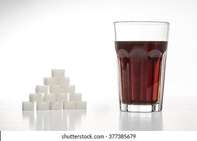 Glass full of soft drink, next to it is the amount of sugar used in it