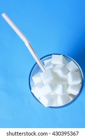 Glass full of sugar cubes with straw. Soft drinks contains to much sugar.