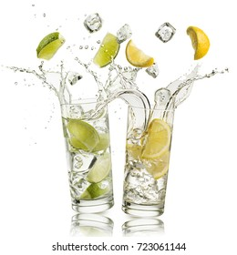 glass full of water with lemon and citron slices and ice cubes falling and splashing water, on white background