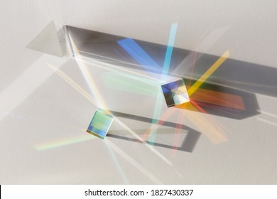 Glass geometric figures prisms with light diffraction of spectrum colors and complex reflection with trendy light and hard shadows on a white background.