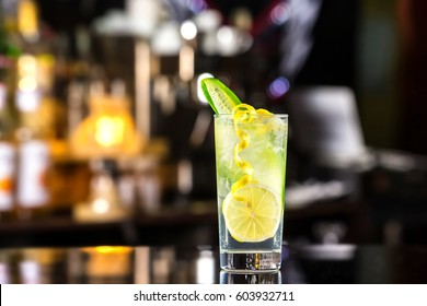 Glass of gin tonic cocktail decorated with cucumber at bat counter background.