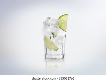 A glass of Gin Tonic cocktail  drink with ice cubes (on the rocks) and a slice of lime. Isolated on white background.