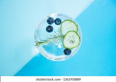 A glass of a gin and tonic drink with blueberries, cucumber and a rosemary twig isolated on abstract, colourful, geometrical color block blue backgound