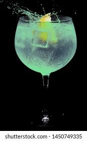 glass of gin tonic green and lemon