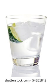 Glass of gin and tonic with ice cubes and lime wedge