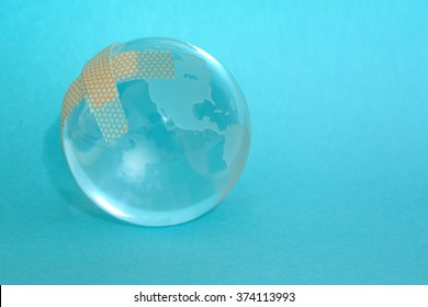 glass globe with band-aid on blue background