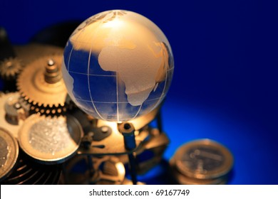 Glass globe lying on gears and coins on dark blue background