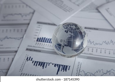 Glass globe on the chart papers.
