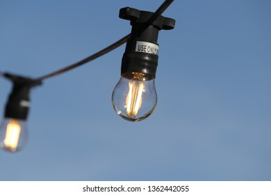 Glass globe patio lightbulb illuminated and strung outdoors on sunny day with clear blue sky in background