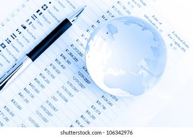 Glass globe and pen on finance chart