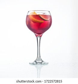 Glass goblet of cold wine with fruit placed on reflective white background