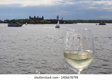 Glass goblet of white wine in foreground with Ellis Island and small boats watercraft in background in early evening as seen from Hudson River.