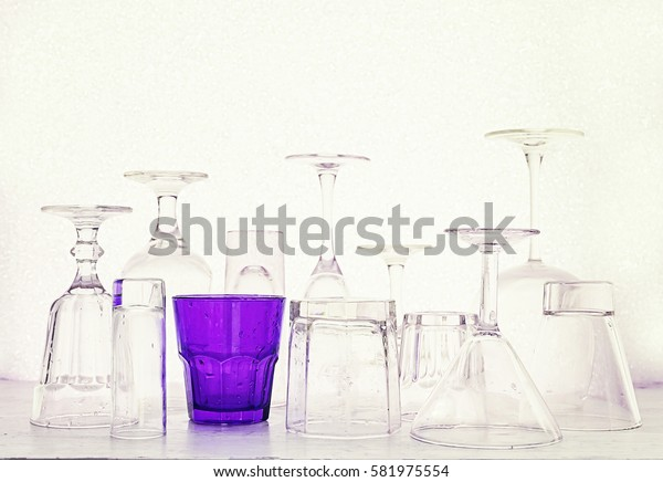 Glass goblets of different shapes and a multi-colored on a white background.