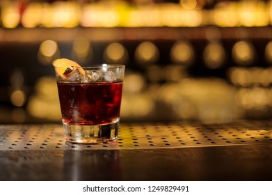 Glass of a Godfather cocktail with orange zest standing on the steel wooden bar counter on the blurred background
