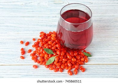 Glass with goji juice on wooden table