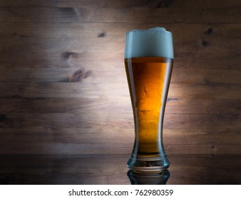Glass of golden beer on wooden background