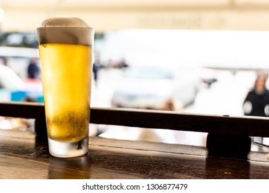 Glass of golden cold beer on counter facing street at restaurant